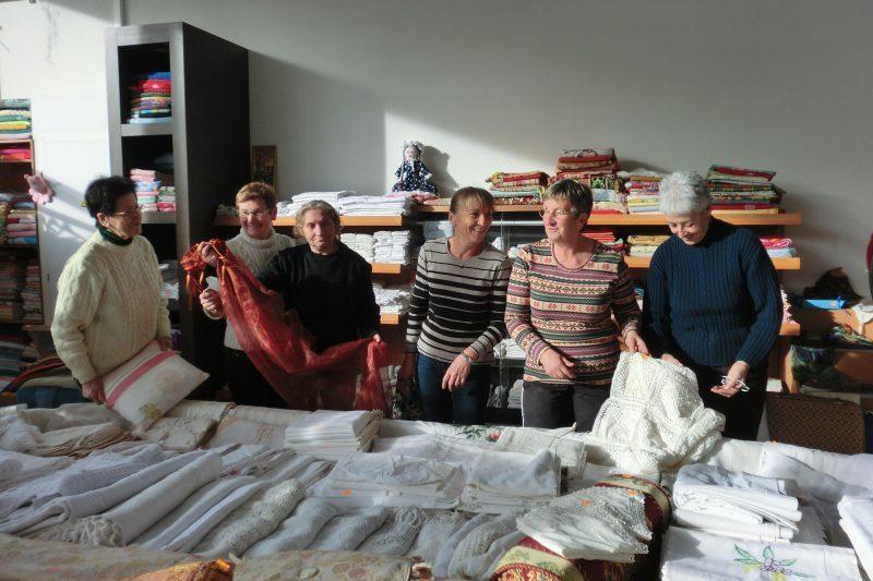 Bénévoles et compagnes préparant ensemble, le stand du linge de maison dans le nouveau hall de vente Emmaüs.