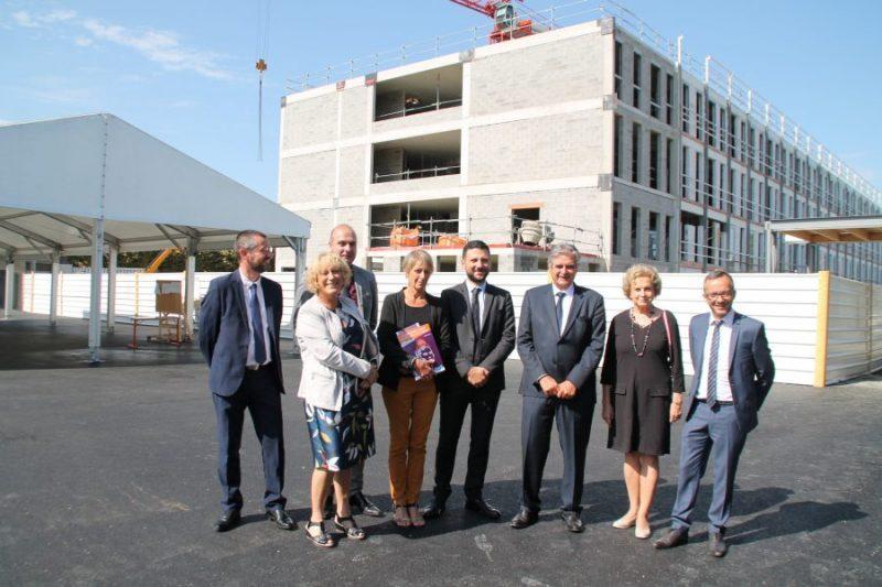 La pose devant le futur bâtiment