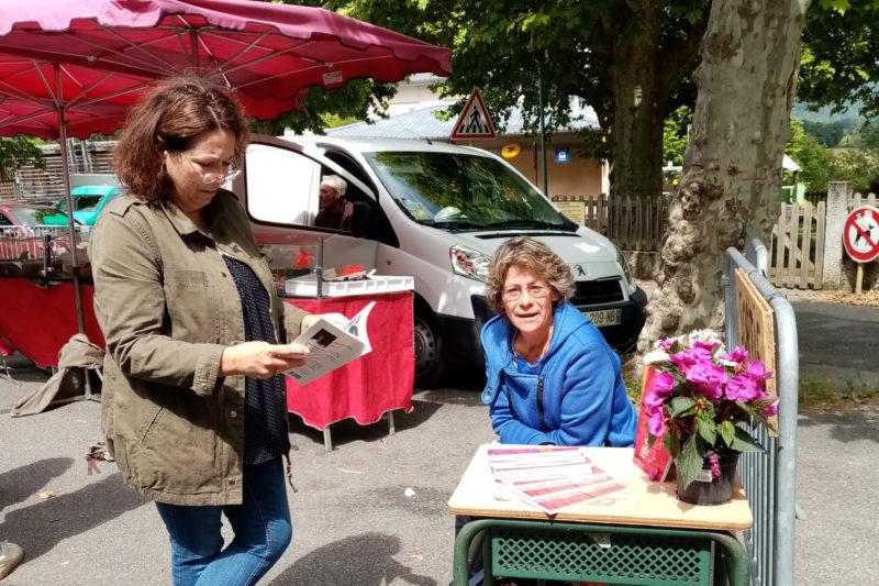 Brigitte Le Moël sur le marché présente son livre.